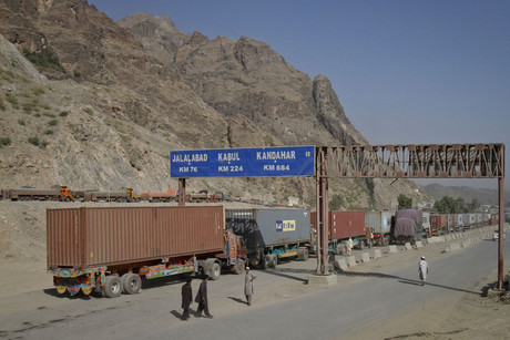 Trucks drive past a road sign showing the distance to cities in Afghanistan from the northwest town of Torkham, at the border crossing to Pakistan (Reuters/Shahid Shinwari)