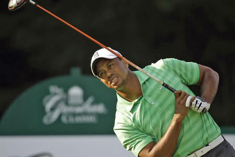 Tiger Woods leans with a tee shot at the 12th