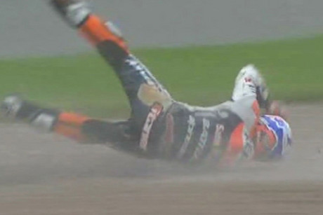 Casey Stoner comes off his bike