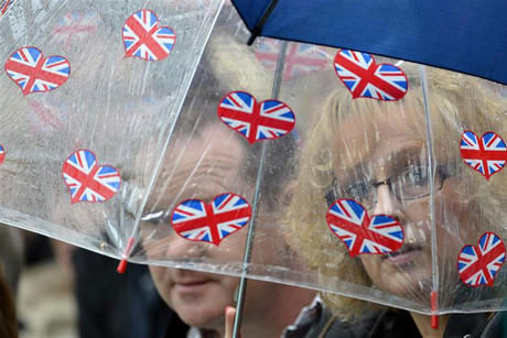 Spectators try to keep dry on Centre Court during the men's singles tennis match between David Ferrer of Spain and Juan Martin del Potro of Argentina at the Wimbledon tennis championships in London (Reuters)