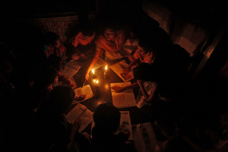 A teacher conducts a lesson for students in the light of kerosene lamps and a candle (Reuters)