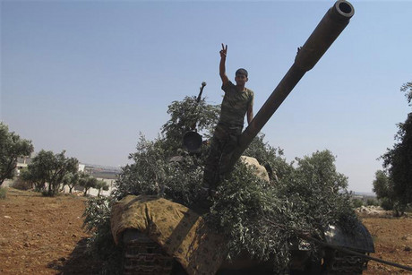 A member of the Free Syrian Army flashes the victory sign on a captured tank after taking control of a checkpoint from government forces in Anadan, north Aleppo (Reuters)