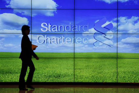 A staff member walks inside a priority banking service area of a Standard Chartered bank (Reuters)