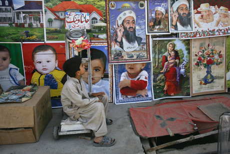 A child looks up at posters depicting the slain al-Qaeda leader Osama bin Laden at a roadside stall in Quetta (Reuters)