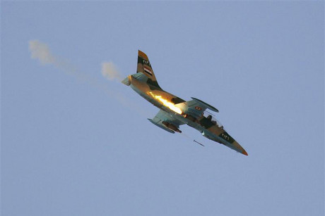 A Syrian Air Force fighter plane fires a rocket during an air strike in the village of Tel Rafat (Reuters)
