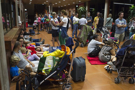 People rest at San Sebastian de la Gomera port after being evacuated from Valle Gran Rey on the Spanish Canary Island of La Gomera (Reuters)