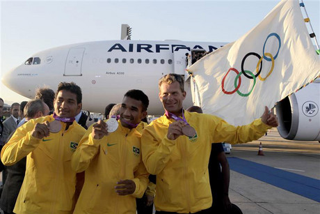 Brazilian athletes pose with their medals after arriving with the Olympic flag from the London 2012 Olympic Games to Rio de Janeiro (Reuters)