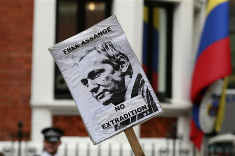 A placard is held by a supporter of Julian Assange outside the Ecuador embassy in west London (Reuters)