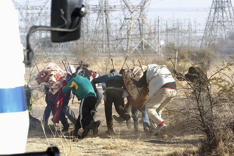 Protesting miners react as the police shot at them outside a South African mine in Rustenburg, 100 km (62 miles) northwest of Johannesburg (Reuters/Siphiwe Sibeko)
