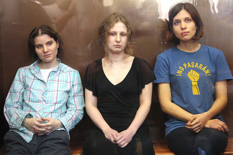 Pussy Riot members Yekaterina Samutsevich (L ), Maria Alyokhina (C) and Nadezhda Tolokonnikova (R) sit in a glass-walled cage in a court room at the Khamovnichesky Court in Moscow, Russia (NZN)