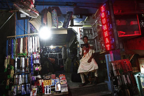 A shopkeeper watches a screen as he waits for customers at his illuminated shop after the electricity was restored (Reuters)
