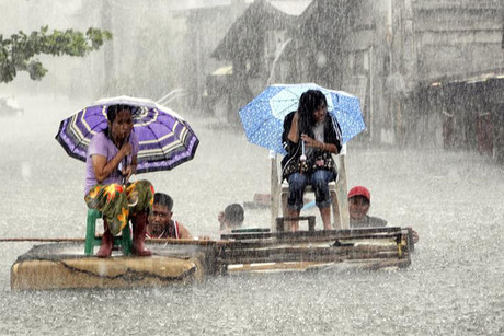Residents ride on a makeshift raft during a heavy downpour in Manila (Reuters)