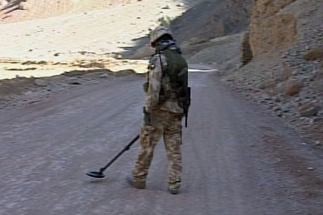 A soldier searches for hidden IEDs