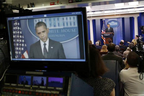 Obama is seen on a television monitor (Reuters)