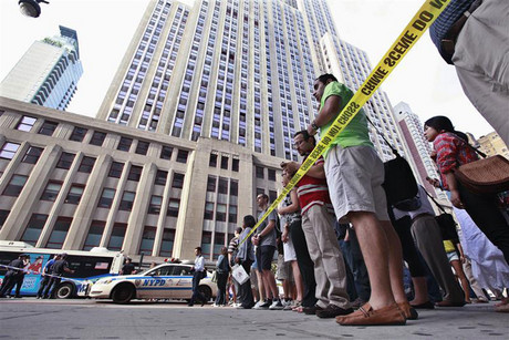 People stand near a police line at the scene of a shooting outside the Empire State Building in New York (Reuters)