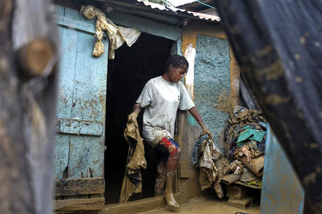 A Haitian woman removes mud-covered clothing from her house which was flooded due to Tropical Storm Isaac in an area outside of Port-au-Prince (Reuters/Swoan Parker)