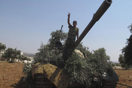 A member of the Free Syrian Army flashes the victory sign on a captured tank (Reuters)