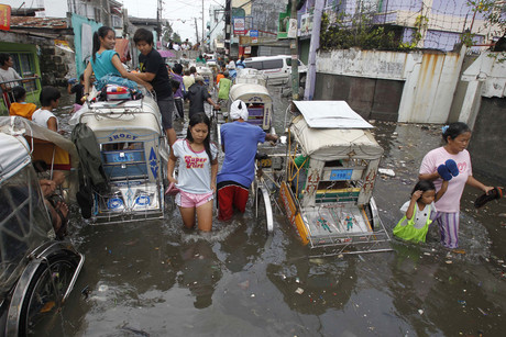 Residents battle with flood waters in Navotas city, north of Manila (Reuters)