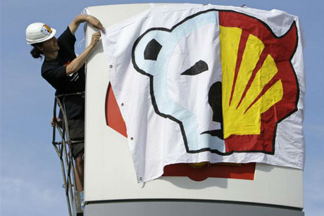 Greenpeace activist hangs a banner on a Shell gas station sign in Prague (Reuters)