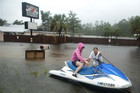 Owners Hank and Lori Plauche use a jet-ski to survey the damage to the Jourdan River Steamer, Seafood Restaurant as Hurricane Isaac passes through Kiln, Mississippi (Reuters)