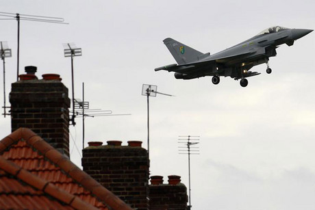 An RAF jet flies over houses in London (Reuters)