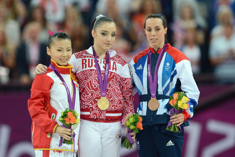 China's silver medalist Kexin He, Russia's gold medalist Aliya Mustafina and Great Britain's bronze medalist Beth Tweddle during the Artistic Gymnastics women's uneven bars final at the North Greenwich Arena, London (AAP)