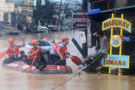 Rescuers evacuate residents from their flooded homes on a rubber boat in Manila (Reuters)