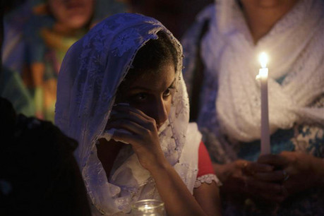A woman cries during a candlelit vigil for those killed in the attack  (Reuters)