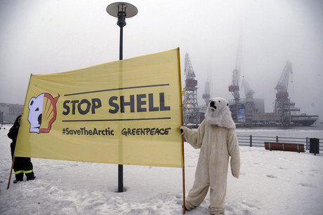 Greenpeace activists hold a banner as they protest against Shell's plans to drill in the Arctic, at a port in Helsinki (Reuters/Markku Ulander)