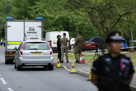 Army and police personnel stand outside the home of Saad al-Hilli in Claygate (Reuters)