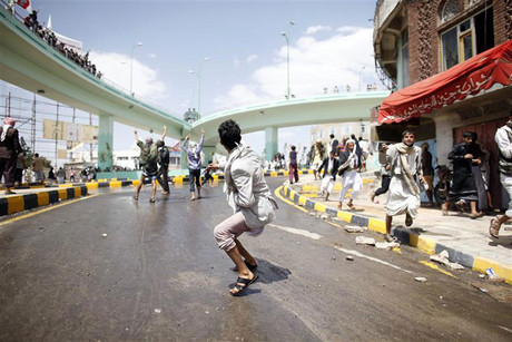 Protesters run as riot police fire tear gas at them outside the US embassy in Sanaa (Reuters)