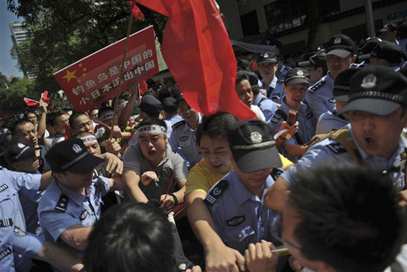 Protesters clash with policemen as they tried to break into a hotel which leads to the Japanese consulate (Reuters)