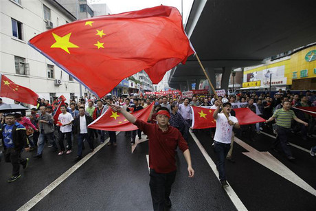 Demonstrators wave Chinese flags as they march during a protest against Japan in Chengdu (Reuters)