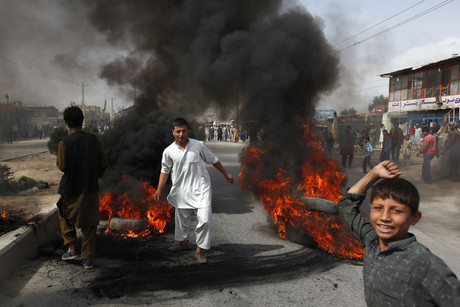 Afghan protesters burn tyres on a street during a demonstration in Kabul over the film (Reuters)