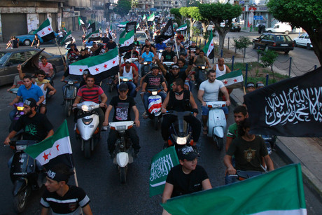 Lebanese Islamists on scooters, wave Syrian Opposition and Islamist flags to express solidarity with Syria's anti-government protesters (Reuters)