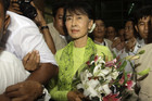 Aung San Suu Kyi walks among her supporters as she arrives at the airport to embark on a trip to the US (Reuters)