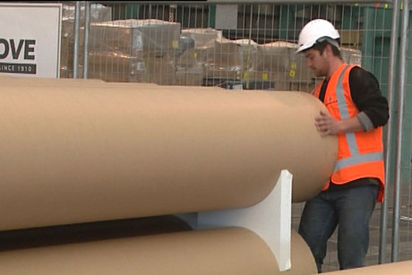 A worker handles the newly arrived cardboard tubes