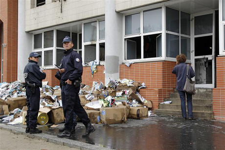 Police stand in front of the damaged offices of magazine Charlie Hebdo last year (Reuters)