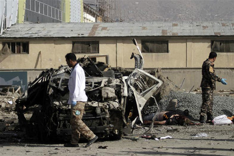 Afghan security personnel stand near a mangled vehicle (Reuters)