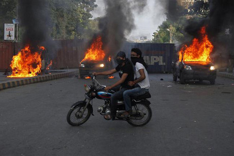 Protestors ride past burning police vehicles in Karachi  (Reuters)