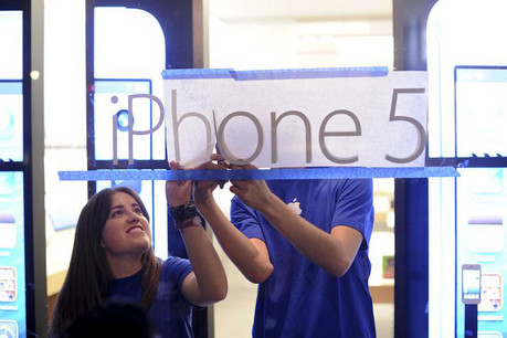 Storekeepers put up a sign before the iPhone launch in San Francisco  (Reuters)