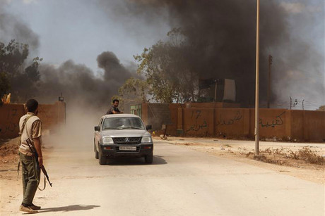 Members of the Rafalla al-Sihati brigade, part of the Libyan army, drive as they check their base which was attacked by demonstrators in Benghazi city (Reuters)