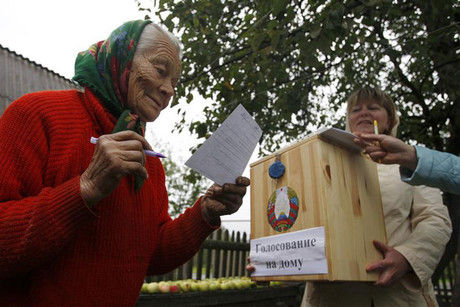 A woman reads a ballot before casting her vote into a portable ballot box during the parliamentary elections in Belarus (Reuters)