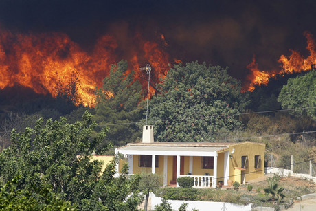 Smoke from a wildfire engulfs a hillside next to a house in Pedralba near Valencia (Reuters)