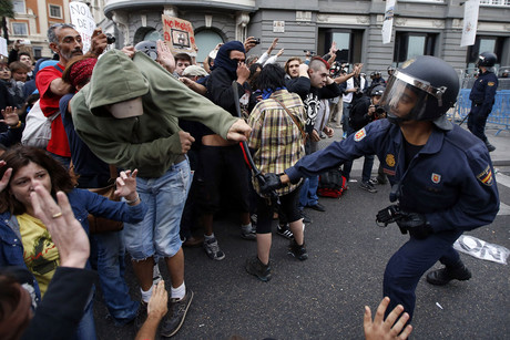 A policeman clubs a protester outside the the Spanish parliament (Reuters)