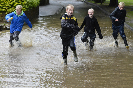 Boys run through flood water in Morpeth (Reuters)
