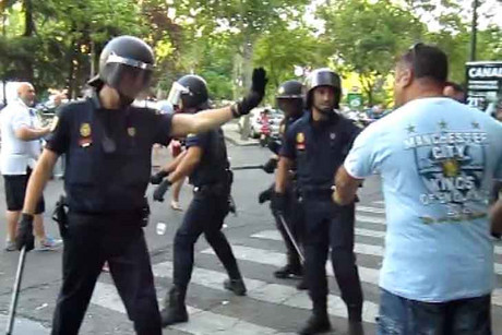 A Manchester City fan reacts to treatment from Madrid police
