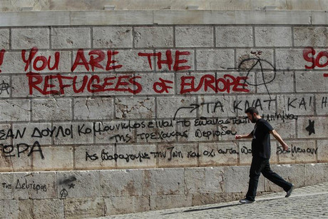 A man walks past graffiti outside the Athens' Academy in central Athens (Reuters/John Kolesidis)