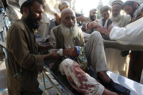 Afghan men assist those injured in a bomb blast as they arrive at a hospital in Jalalabad (Reuters)