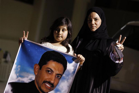 Arrested human rights activist Nabeel Rajab's wife Sumaya and daughter Malak hold a picture of jailed uprising leader Abdulhadi al-Khawaja (Reuters)